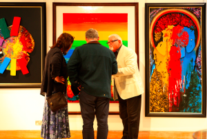 Gültekin Bilge discussing paintings at one of his art exhibitions